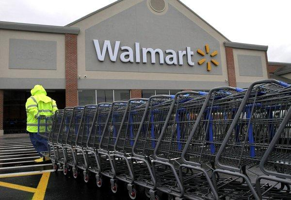 A worker pulls a line of shopping carts toward a Wal-Mart store in North Kingstown, R.I.