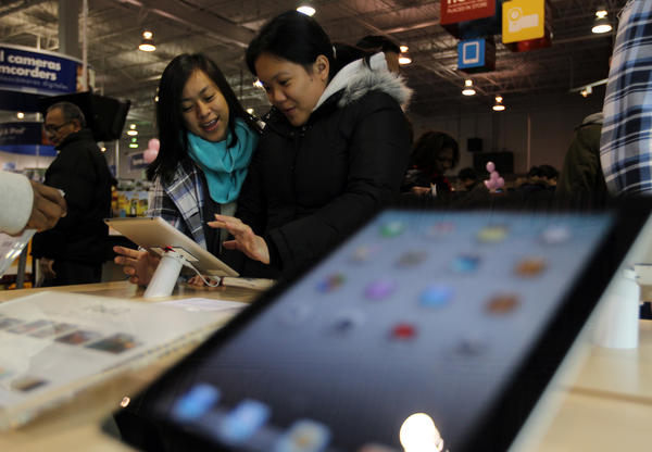 Customers play with an iPad 2 while shopping for electronics on Black Friday at Best Buy in Schaumburg in 2011. You can use social media to find Black Friday deals this year.