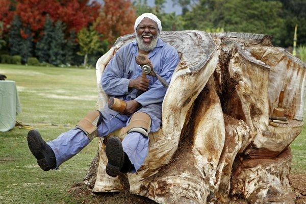 Compton sculptor Charles Dickson takes a break from carving a bench from this earpod, a South American tree with a trunk that was 5 feet in diameter, on the grounds of the Los Angeles County Arboretum and  Botanic Garden in Arcadia.