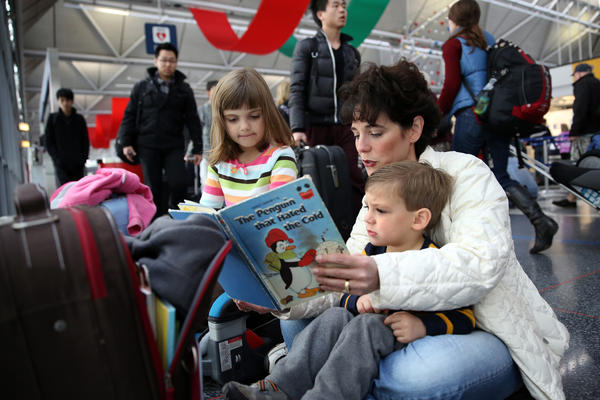 Kristen Turner, of Naperville, reads a book to her son, Gavin, 2, and daughter, Charlotte, 6, at the United Airlines terminal at O'Hare International Airport, as they wait out a two-hour delay to Atlanta. Morning fog is causing flight delays and cancellations on one of the busiest travel days of the year.