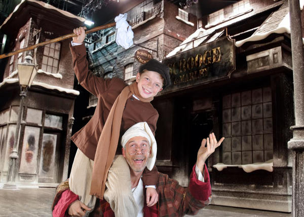"Scrooge (Alan Ware) gives Tiny Tim (Marcus Fleishel) a lift in ""Scrooge: The Musical"" at the Athens Theatre in DeLand."