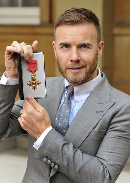 Take That singer Gary Barlow holds his Order of the British Empire, for services to the entertainment industry and to charity, which was awarded to him by Queen Elizabeth.