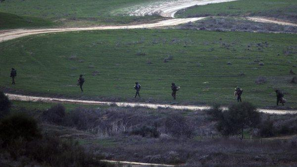 Israeli soldiers walk at dusk near the border with the Gaza Strip.