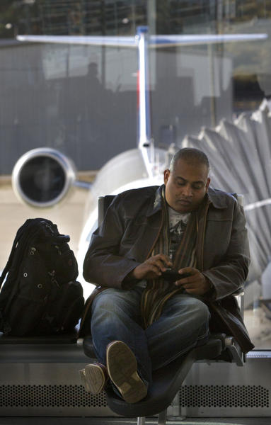 Brian Tillekeratne of Toronto, Canada checks his phone as he awaits a flight to Atlanta where he will connect with flights leading to Toronto, Canada. Tillekeratne was in town on business and was hoping to make it home in time for Thanksgiving. All flights from the airport are booked for the holiday weekend.