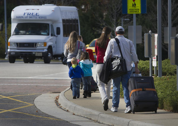 Travelers make their way to the parking lot after arriving at Newport News Williamsburg International Airport Wednesday around midday. All flights from the airport are booked for the holiday weekend.