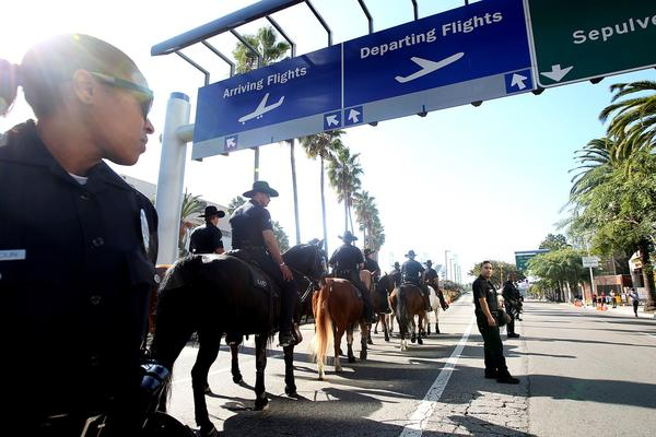 L.A. police officers on horseback head toward Los Angeles International Airport, where a labor march created traffic disruptions on the day before Thanksgiving.