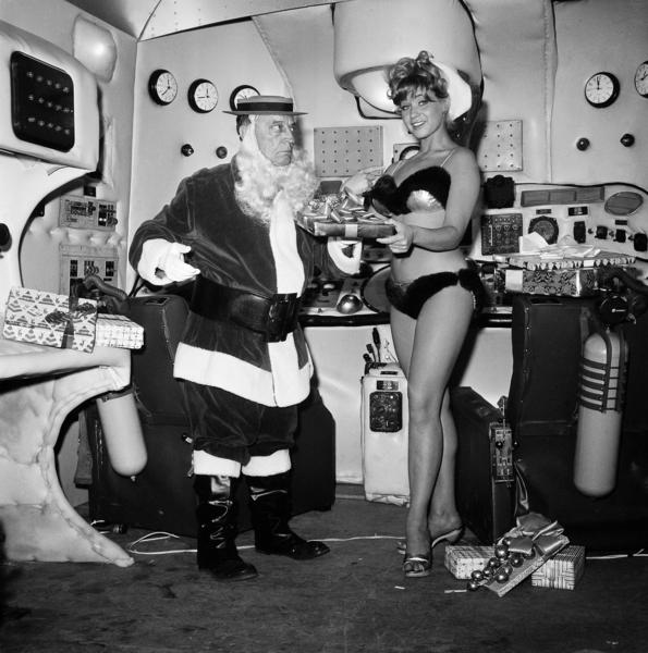"Buster Keaton, comic film actor from the silent era, dressed as Santa Claus, and Bobbi Shaw as Santa's helper are on the set of ""Beach Blanket Bingo"" in Los Angeles on Dec. 17, 1964."