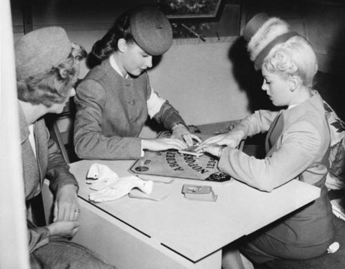 "June Lockhart, left, watches Lana Turner and Susan Peters use a Ouija board between scenes of their film, ""Keep Your Powder Dry,"" on Nov. 12, 1944."