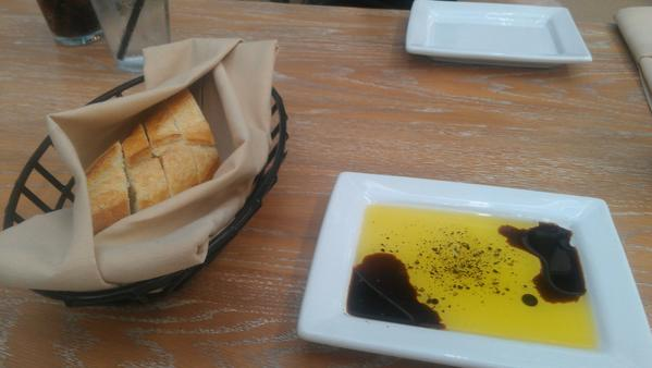 A bread basket with oil and vinegar is served to start.