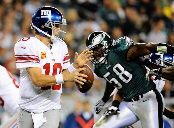 New York Giants quarterback Eli Manning (10) is pressured by Philadelphia Eagles defensive end Trent Cole (58) at Lincoln Financial Field in Philadelphia on Sunday November 30, 2012.