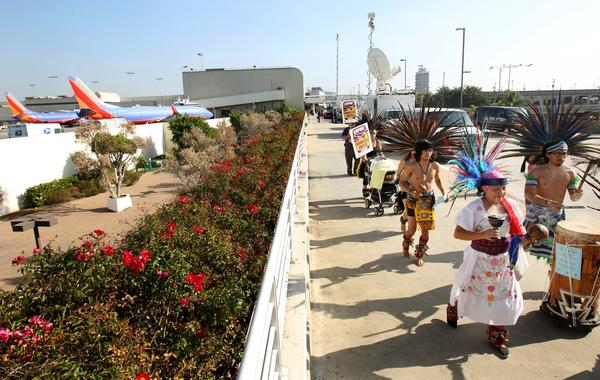 Cuauhtemoc Aztec dancers take part in the march through LAX.