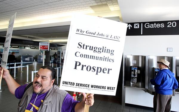 United Service Workers West organizer Adrian Alvarez marches with a small group through LAX.