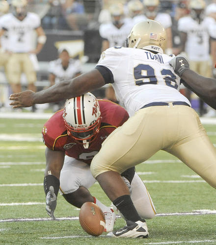 Terps running back Davin Meggett fumbles while being pursued by Navy's Jabaree Tuani in the second half.