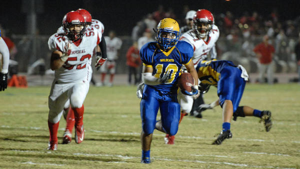 Brawley Union High running back Issak Comparan (right) runs for a large gain against Imperial High on Friday in Brawley. With the win, the Wildcats advanced to the CIF-San Diego Section Division IV semifinals against Madison High.