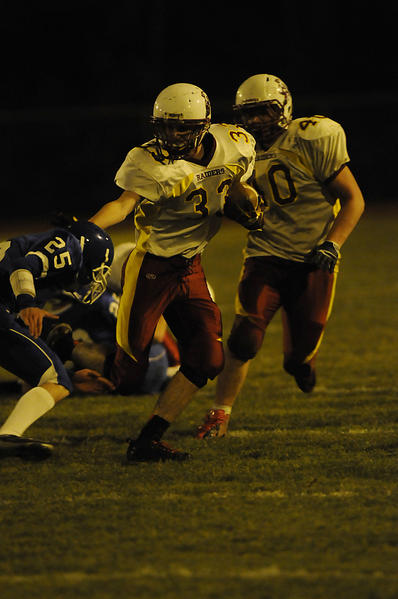 Windsor Locks' Jake Lareau, #33, center, fends off Stafford's Logan Frassinelli, #25, left, during the game played at Stafford High Friday night.