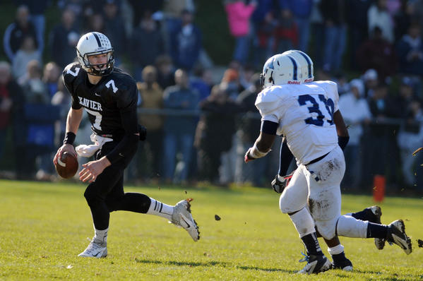 Xavier quarterback Tim Boyle (7) looks for an open man while under pressure from Middletown's Yaamal Jackson and Akeino Chamberlain at Andrus Field at Wesleyan University in Middletown on Thanksgiving Day. Boyle completed 19 of 24 passes for 275 yards in Xavier's 41-14 victory to end the regular season, 9-1.