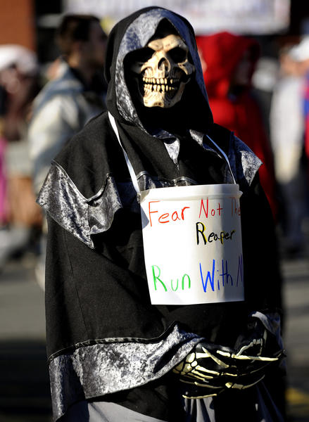 """Fear Not the Reaper, Run With Me"" is what Chris Greenwell of Cheshire wrote on a placard as he dressed as the Grim Reaper for the 76th running of the Manchester Road Race on Thanksgiving Day."
