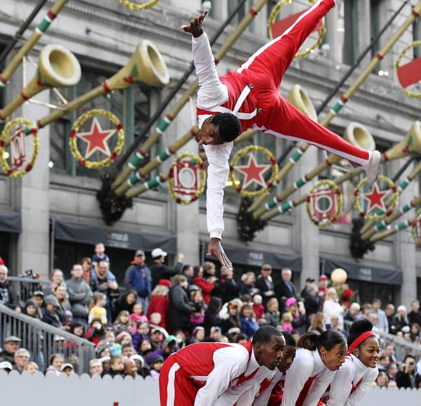 A member of the Jesse White Tumbling Team flies over his teammates.