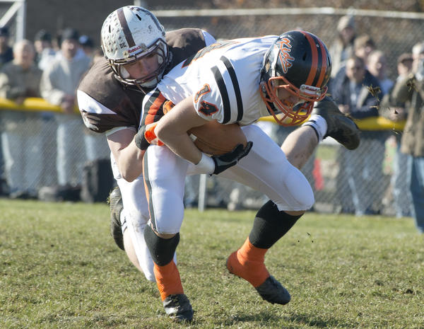 Catasauqua High School's Rhaine Sziv (left) stops Northampton's Kyle George, who carries the ball during Thanksgiving Day Football game at Catasauqua High School's Alumni Field on Thursday. /