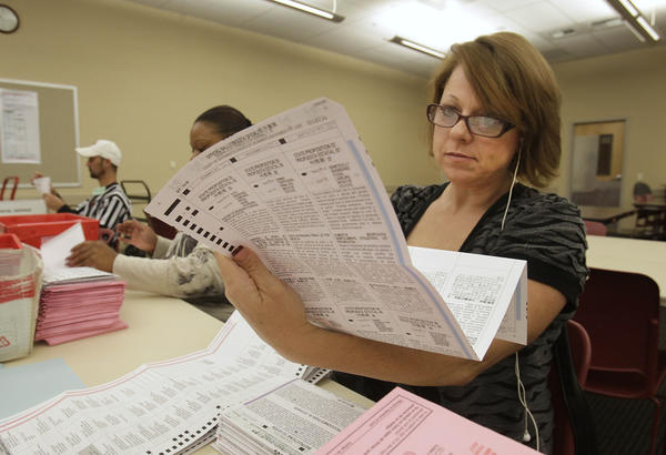 Victoria Williams processes a mail-in ballot at the Sacramento County Registrar of Voters office in Sacramento, Calif.