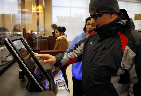"Vasel Popov uses the new touch-screen ATM at the ""self-service banking kiosk"" at Chase's branch at 6155 N. Western Ave. The new ATMs allow customers to select the quantity and dollar value of the bills they withdraw."