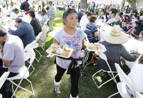 Monalyn Tarin, who is homeless in Pasadena, looks for her son carrying two plates of food through a crowded dining area at Central Park in Pasadena where Union Station Homeless Services served over 6,000 meals for the 35th Thanksgiving Dinner-in-the-Park on Thanksgiving on Thursday, November 22, 2012.