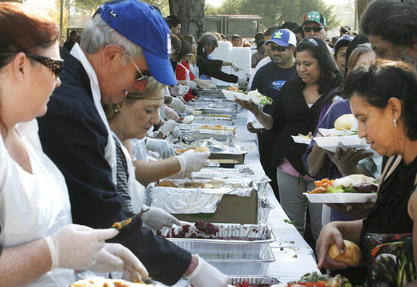 One of several long tables with servers on one side, and a steady stream of people hungry for a Thanksgiving meal at Central Park in Pasadena where Union Station Homeless Services served over 6,000 meals for the 35th Thanksgiving Dinner-in-the-Park on Thanksgiving on Thursday, November 22, 2012.