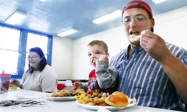 Kayla, Bryson and Daniel Robinson of Hagerstown enjoy a Thanksgiving dinner at Memorial Recreation Center in Hagerstown on Thursday. The inaugural Community Partnership Event was hosted by a number of local churches and nonprofit organizations.