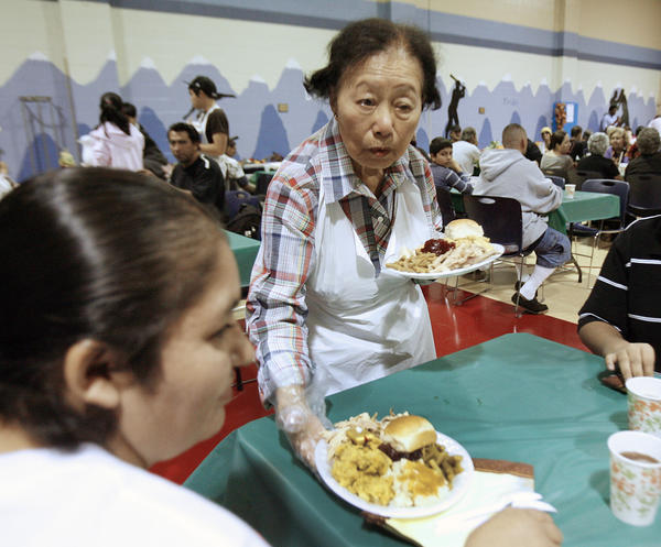 Volunteer Alice Ling, of Glendale, with the Women's Home Leage of the Salvation Army, serves two plates of food to a table at the Glendale Salvation Army where over 250 meals were served with the help of volunteers and community partners on Thanksgiving on Thursday, November 22, 2012.