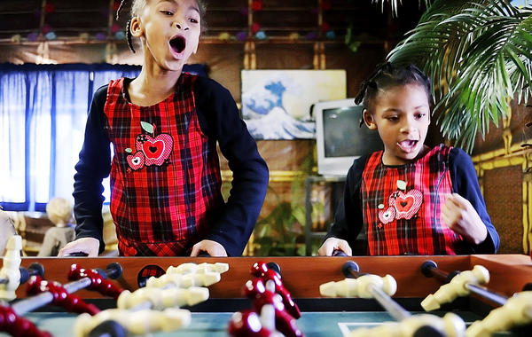 Tiahya, left, and Zoey Lomax react to scoring during a game of foosball before a Thanksgiving Day meal at The Hope Center Rescue Mission off North Prospect Street in Hagerstown.