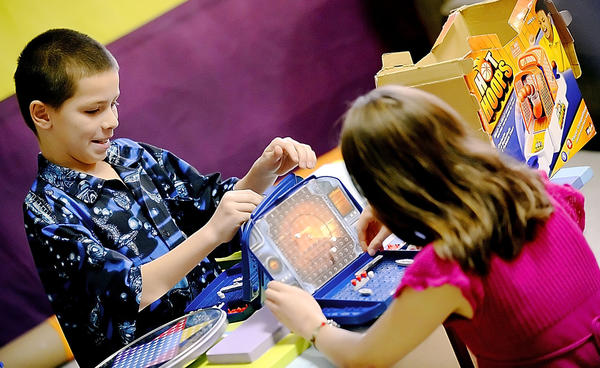 Jason Perez, left, plays Battleship with Emily Hadigian before a Thanksgiving dinner at The Hope Center Rescue Mission off North Prospect Street in Hagerstown.