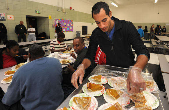 Tim Shelton, a University of Maryland School of Social Work student, serves a slice of pie to Craig Thornton, center (looking at pie cart) at Booker T. Washington Middle School.