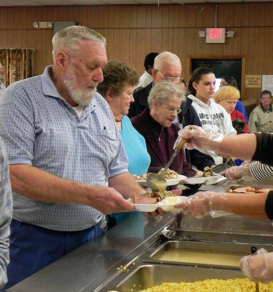 People line up to be served at the Metcalfe family's ninth annual Thanksgiving dinner at Lemasters Community Center. More than 1,177 people attended, making it the largest dinner so far.