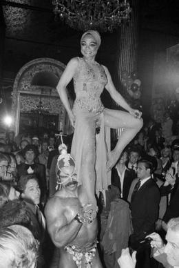 "Eartha Kitt, star of the Broadway Play ""Timbuktu"", arrives on the shoulders of Tony Carroll, Mr. Universe of 1977, at New York's Waldorf Astoria."