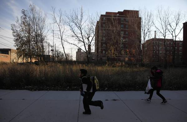 Children walk by a vacant lot on West Cullerton Street, home to hazardous levels of brain-damaging lead.