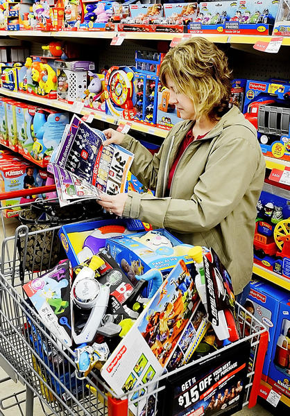 Amy Martin of Smithsburg looks over a sales flier while shopping for toys at Kmart in Hagerstown on Thanksgiving Day. Martin was buying toys for the Fraternal Order of Police Christmas party.