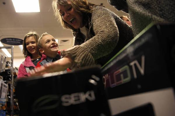 Terri Schroeder, of Chicago, is thrilled with scoring two televisions Thursday night as her children, Ryan, 6, and Katie, 9, look on at Sears in Woodfield Mall in Schaumburg. The store opened at 8 p.m. on Thanksgiving.