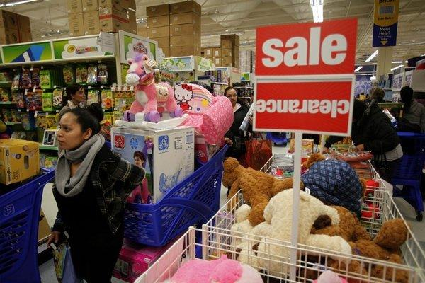 Black Friday shoppers lined up and rushed into a Torrance Toys R Us on Thanksgiving evening. Many retail stores are pushing their opening times earlier and earlier each year. Customers roam the store's aisles with overflowing shopping carts.
