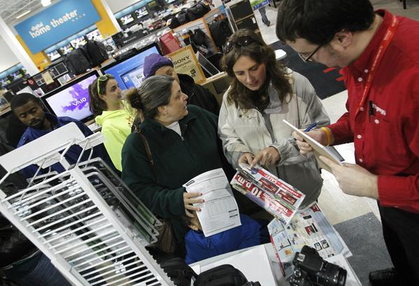 Crystal Ballance speaks with Jonathan Shanks (right) while waiting in line to purchase tablets, cameras and mp3 players during a Black Friday shopping event at h.h.gregg in Newport News on Thursday night.