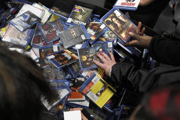 Best Buy shoppers in Aurora, Ill., look through discount DVDs after the store let in customers earlier than the scheduled midnight opening.