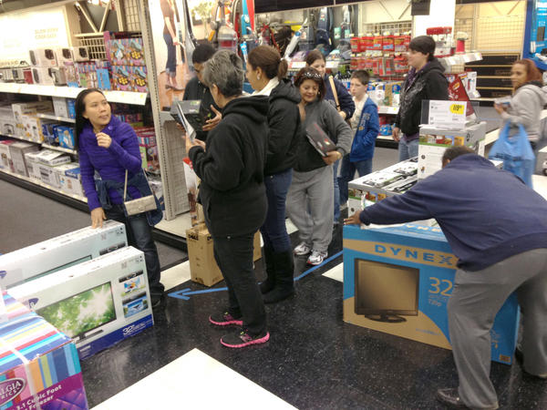 Black Friday shoppers form a line at Best Buy after picking out flat-screen televisions, tablets, video game consoles and games, movies, and other discounted items in the early morning hours.