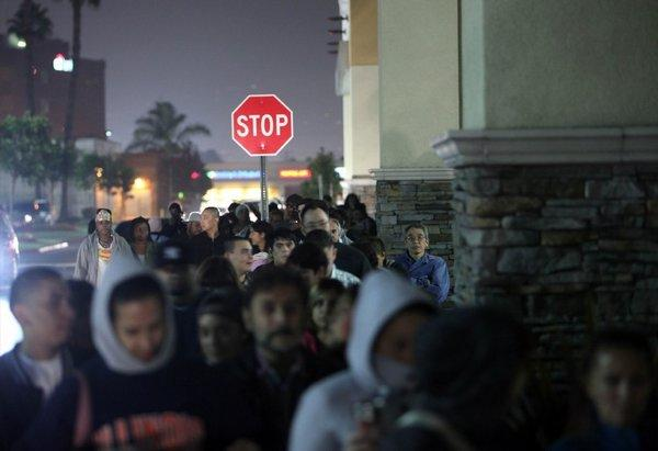 Customers line up outside a Toys R Us for Black Friday deals.