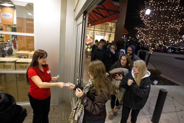 Store manager Julie Walker gives out gift cards to early morning bargain hunters at the 5 a.m. opening of Sports Authority at Yorktown Center Mall.