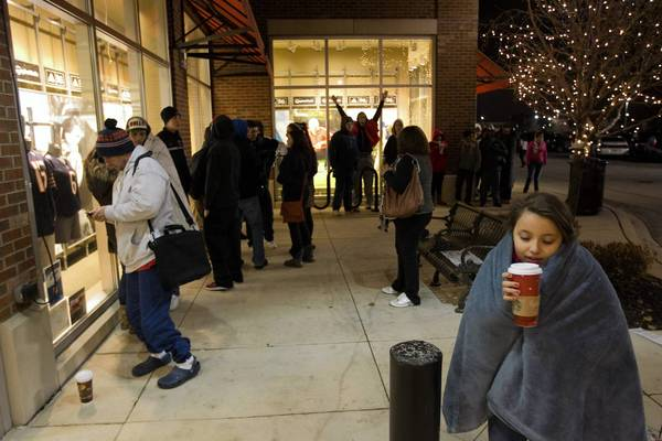 Karla Serrano of Chicago sips a hot drink as she joins a line for the 5 a.m. opening of Sports Authority at Yorktown Center Mall.