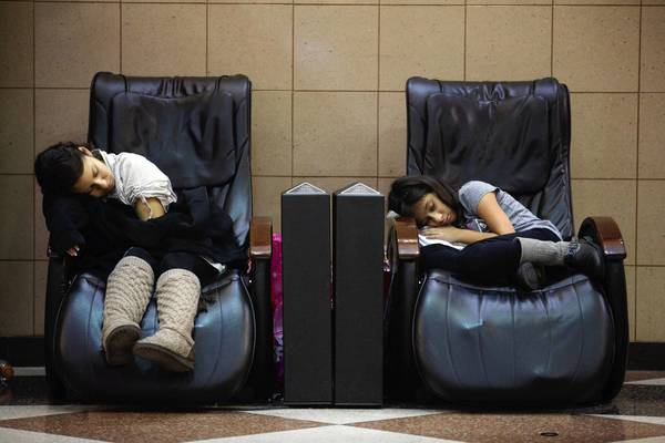 Cousins Karen Reyes, 17, left, and Juana Reyes, 10, of Chicago sleep on massage therapy chairs after a long night of shopping at Yorktown Center Mall. They had been there since midnight shopping with an older relative.