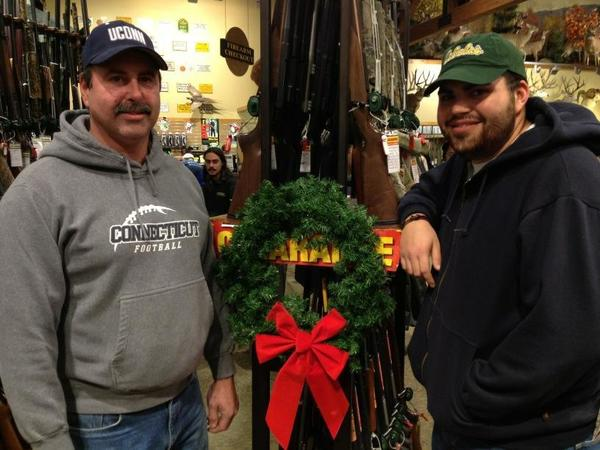 Stephen Nadolny, 47, of West Suffield and his son, Thomas, wait in the gun section of Cabela's for an $800 Browning A-bolt Medallion rifle. Stephen won the rifle for free as one of the first 600 to line up on Black Friday at the East Hartford mega-store. Nadolny waited at least an hour for the store to run the usual gun background checks before he could get the rifle.