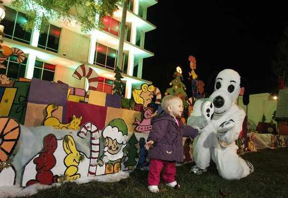 Raeghan Thompson plays with Snoopy during the lighting of the Snoopy House at Costa Mesa City Hall last year.