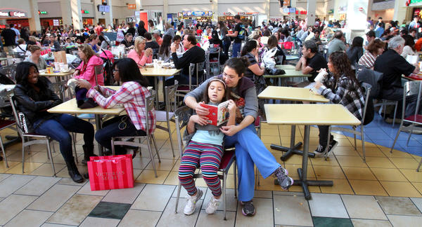 A parent takes a break, as shoppers pack the Florida Mall food court on Black Friday, November 23, 2012, in Orlando.