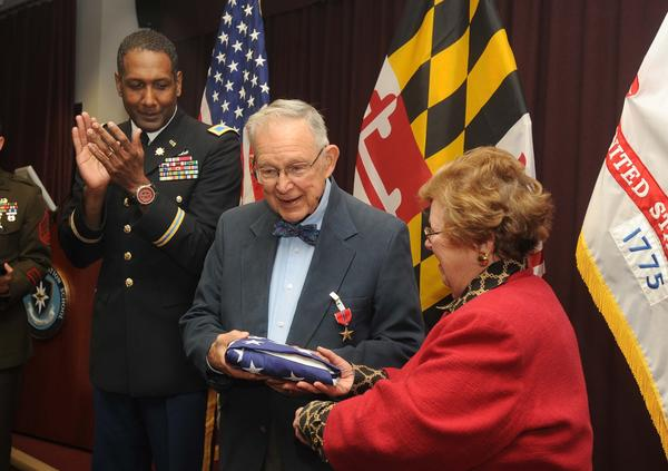 Col. Jeremy Martin, left, applaudes as Senator Barbara Mikulski, right, presents an American Flag to World War II Veteran Dr. Charles E. Rath, 93, after receiving his Bronze Star Medal at Fort Meade Friday morning.