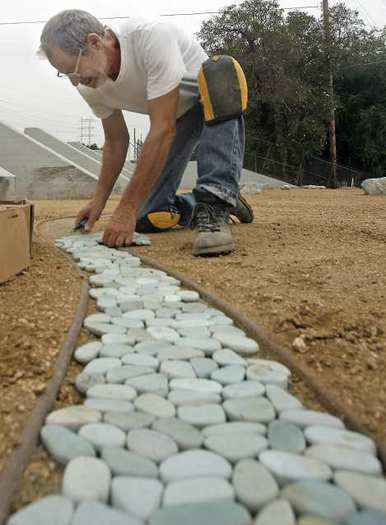 Artist Robert Rossoff lays a flat bed of river rock in the soon to be completed Glendale Narrows Riverwalk Park by the L.A. River in August.